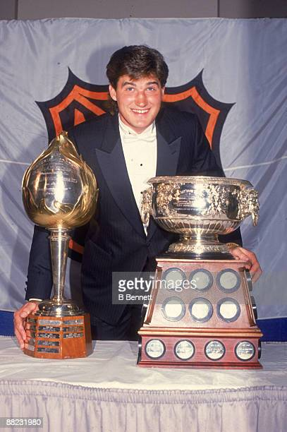 Portrait of Canadian ice hockey player Mario Lemieux at the NHL awards ceremony as he poses with two trophies the Hart Memorial Trophy and the Art...