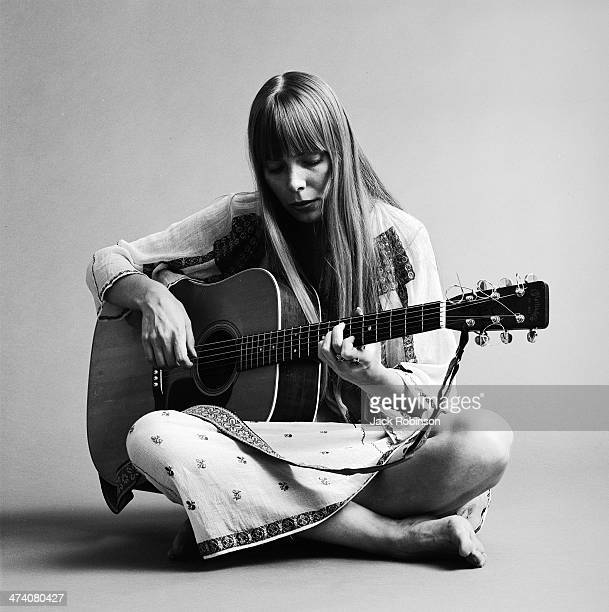 Portrait of Canadian musician Joni Mitchell seated on the floor playing acoustic guitar November 1968 This image is from a shoot for the fashion...