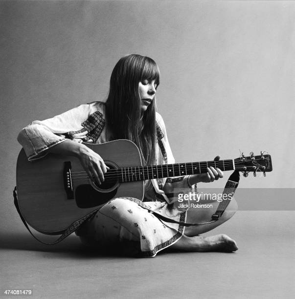 Portrait of Canadian musician Joni Mitchell seated on the floor playing acoustic guitar, November 1968. This image is from a shoot for the fashion...