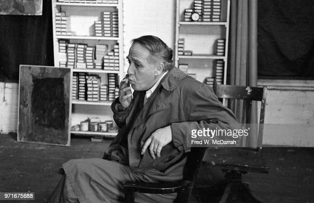 Portrait of Canadianborn American abstract expressionist painter Philip Guston as he sits in a chair and smokes a cigarette in his studio New York...
