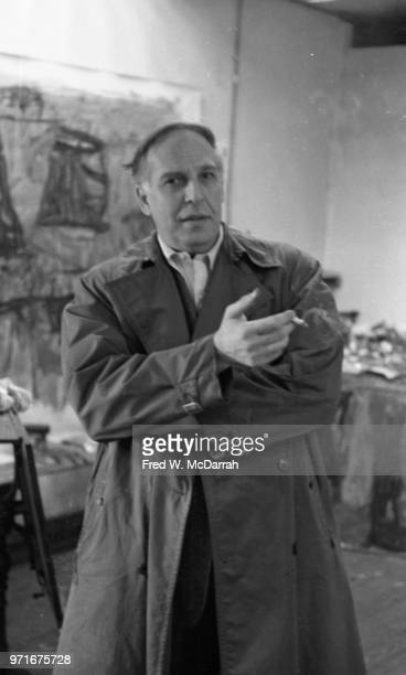 Portrait of Canadianborn American abstract expressionist painter Philip Guston as he stands and guestures a cigarette in one hand in his studio New...