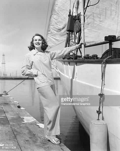 Portrait of Canadianborn American actress and model Deanna Durbin as he poses on a dock beside a sailboat circa 1950
