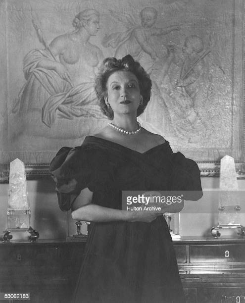 Portrait of Canadianborn beautician and cosmetics entrepreneur Elizabeth Arden dressed in a ball gown as she clasps her hands together and stands in...
