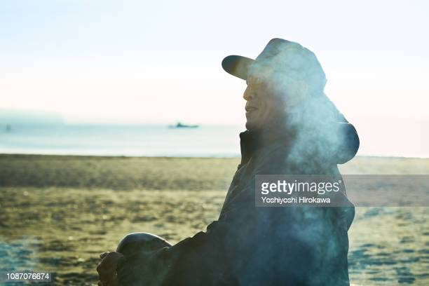 Portrait of canoe player sitting on beach at the morning.