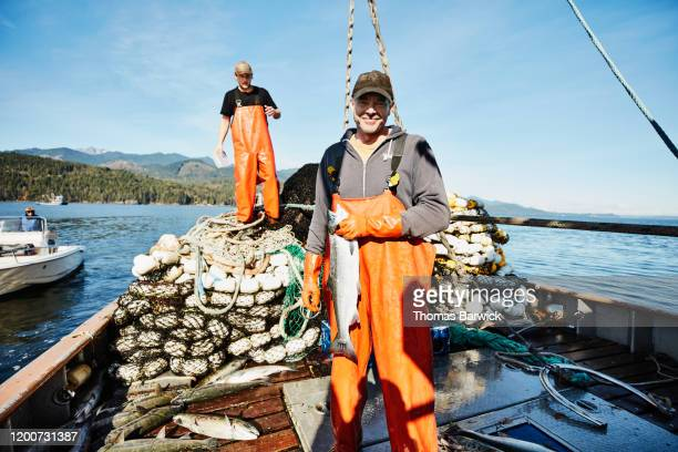 portrait of captain of purse seiner holding coho salmon - nautical vessel stock pictures, royalty-free photos & images
