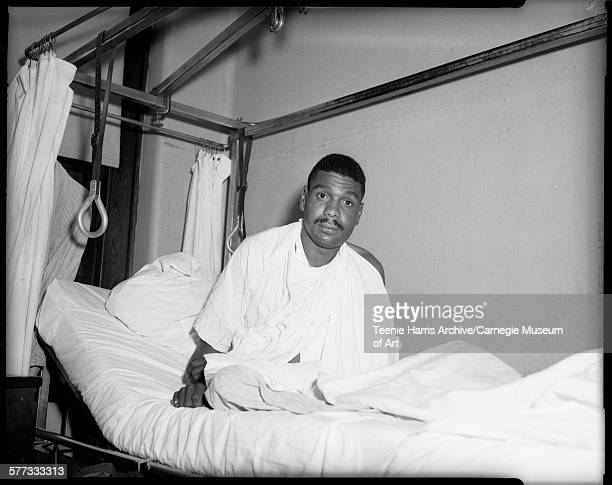 Portrait of car accident survivor Robert Stokes wearing sling and cast on left arm seated on hospital bed Pittsburgh Pennsylvania September 1963