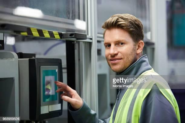 Portrait of car engineer using control panel