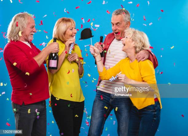 portrait of carefree seniors celebrating new years eve - 55 59 years stock pictures, royalty-free photos & images