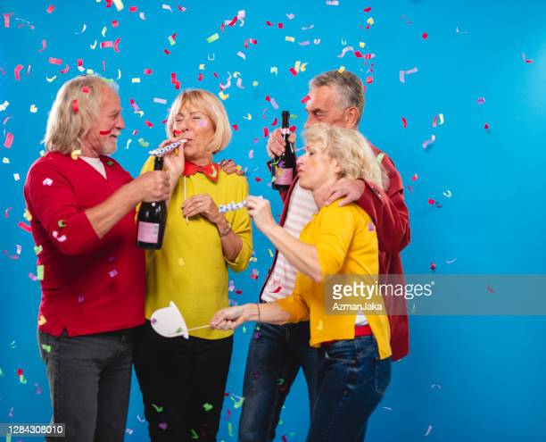 portrait of carefree seniors celebrating new year's eve - 55 59 years stock pictures, royalty-free photos & images