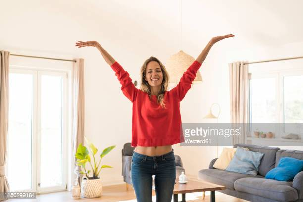 portrait of carefree woman at home - arms raised stock pictures, royalty-free photos & images