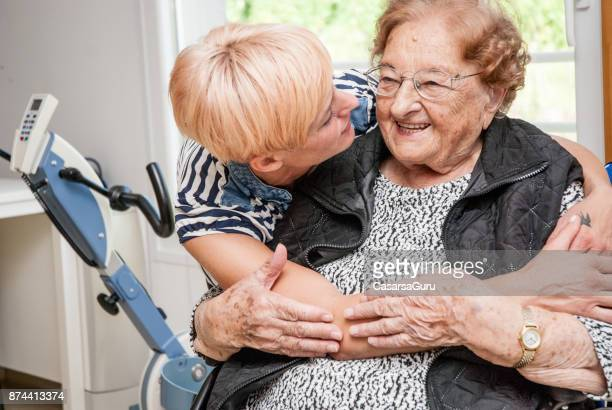 portrait of caregiver in the retirement home embracing senior woman - vulnerability stock pictures, royalty-free photos & images