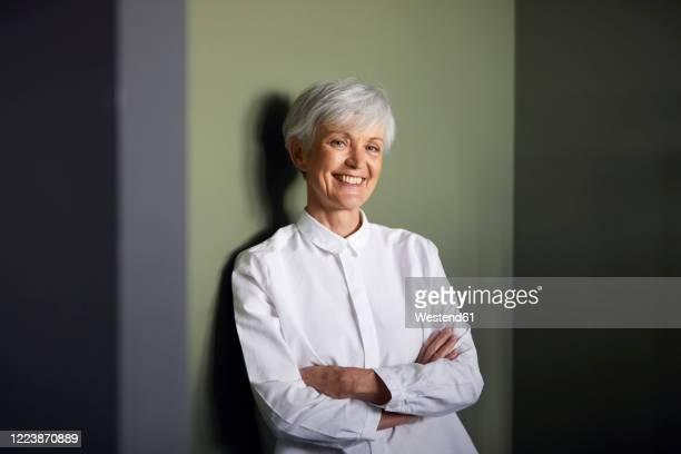 portrait of carfree senior businesswoman leaning against wall - 60 64 jahre stock-fotos und bilder