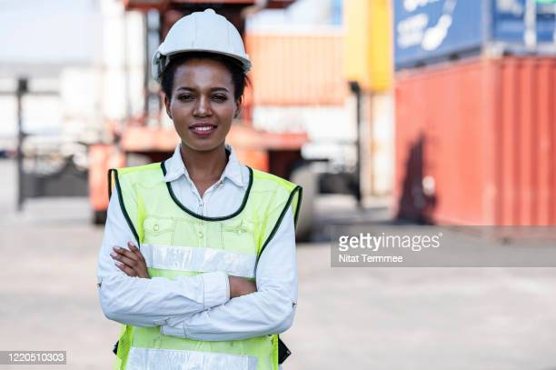 portrait of cargo management afro woman wearing safety protective while standing with her arms crossed in front of large cargo container. - helmet stock pictures, royalty-free photos & images