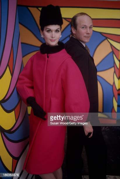 Portrait of Carmen Dell'Orefice in a red coat with a black fur collar a black hat and gloves as she poses with an unidentified man in front of a Pop...