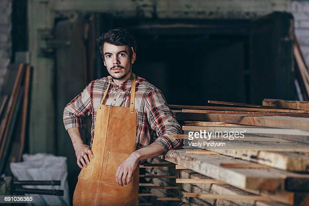 portrait of carpenter standing by timber stack in workshop - craftsperson stock pictures, royalty-free photos & images
