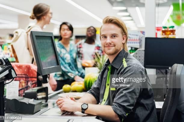 portrait of cashier sitting at checkout - kassierer stock-fotos und bilder