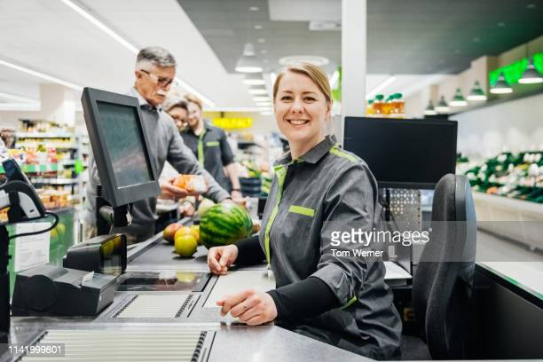 portrait of cashier smiling while working - cashier stock pictures, royalty-free photos & images