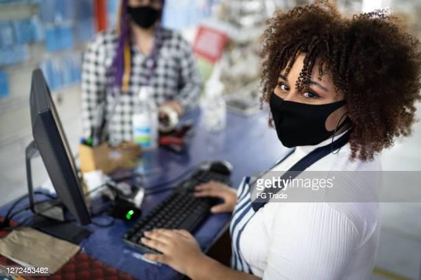 店内で働くフェイスマスクを着用したレジ係の肖像 - ギフトショップ ストックフォトと画像