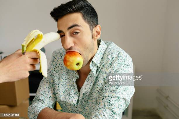 Portrait of casual businessman with banana at temple and apple in mouth