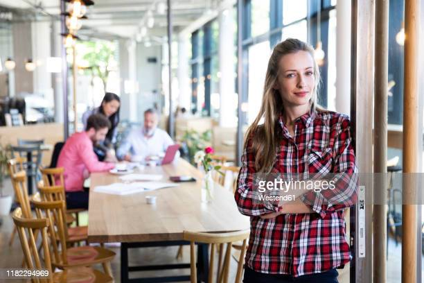 portrait of casual businesswoman in a cafe with colleagues having a meeting in background - 創始者 ストックフォトと画像