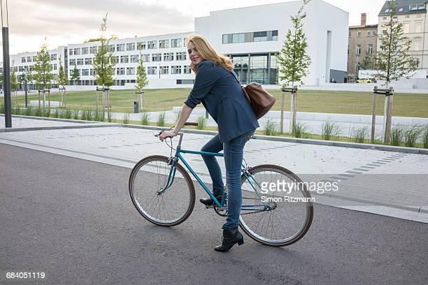 portrait of casual businesswoman on bicycle - blazer vert photos et images de collection