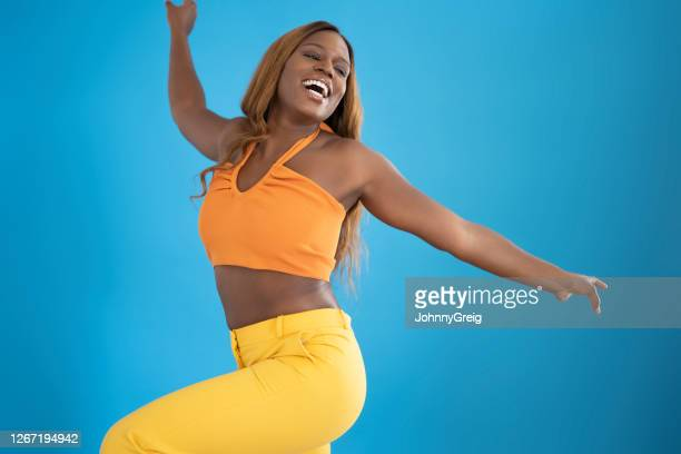 portrait of casual mid 20s black woman smiling and dancing - crop top stock pictures, royalty-free photos & images