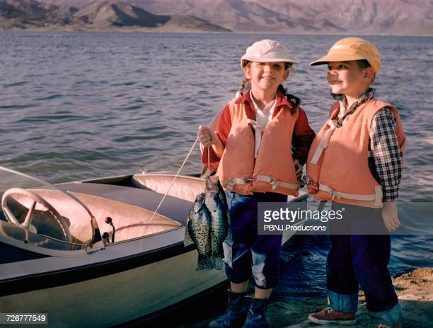 portrait of caucasian brother and sister posing with fish near boat - film d'archive photos et images de collection