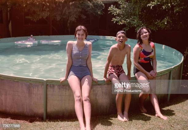 Portrait of Caucasian brother and sisters leaning on swimming pool