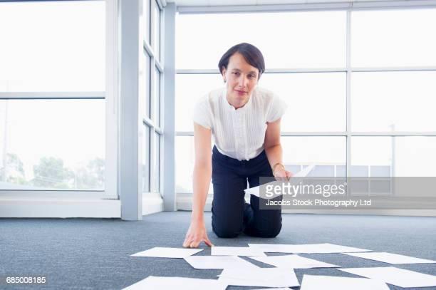 Portrait of Caucasian businesswomen kneeling on floor arranging paperwork