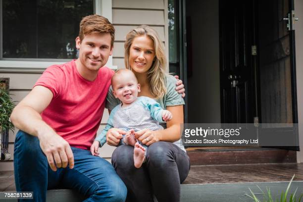 portrait of caucasian couple with baby son sitting on porch - australia photos stock photos and pictures