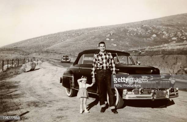 portrait of caucasian father and daughter posing near vintage car - archiefbeelden stockfoto's en -beelden