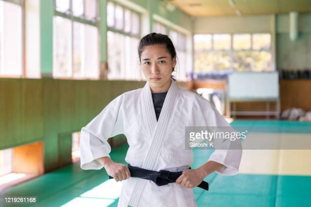 portrait of caucasian female judo athlete fastening black belt - judo stock pictures, royalty-free photos & images