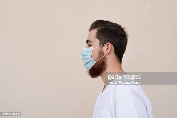portrait of caucasian male nurse with beard and black hair wearing face mask and white suit with yellow wall background - beard stock pictures, royalty-free photos & images