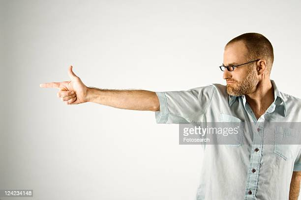Portrait of Caucasian man holding hand out like a gun standing against white background.