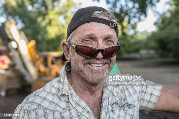 portrait of caucasian man wearing sunglasses and baseball cap - bending over backwards stock photos and pictures