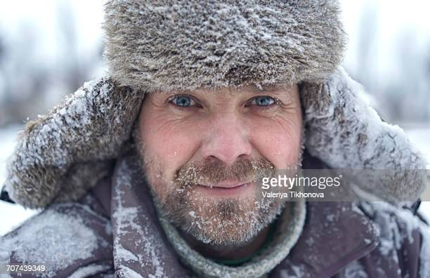 Portrait of Caucasian man with ice in bear in winter