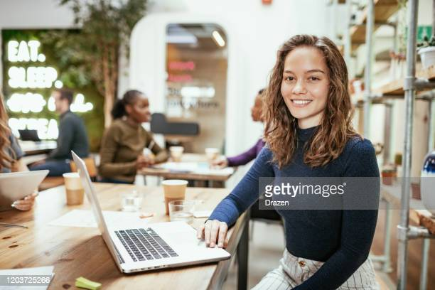 portrait of caucasian millennial woman in office with laptop - looking at camera stock pictures, royalty-free photos & images