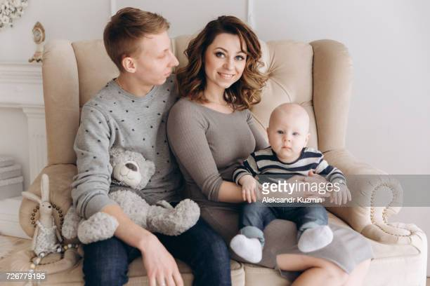 Portrait of Caucasian mother and father on love seat with baby son