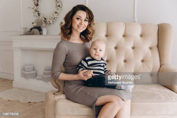 Portrait of Caucasian mother sitting on love seat with baby son