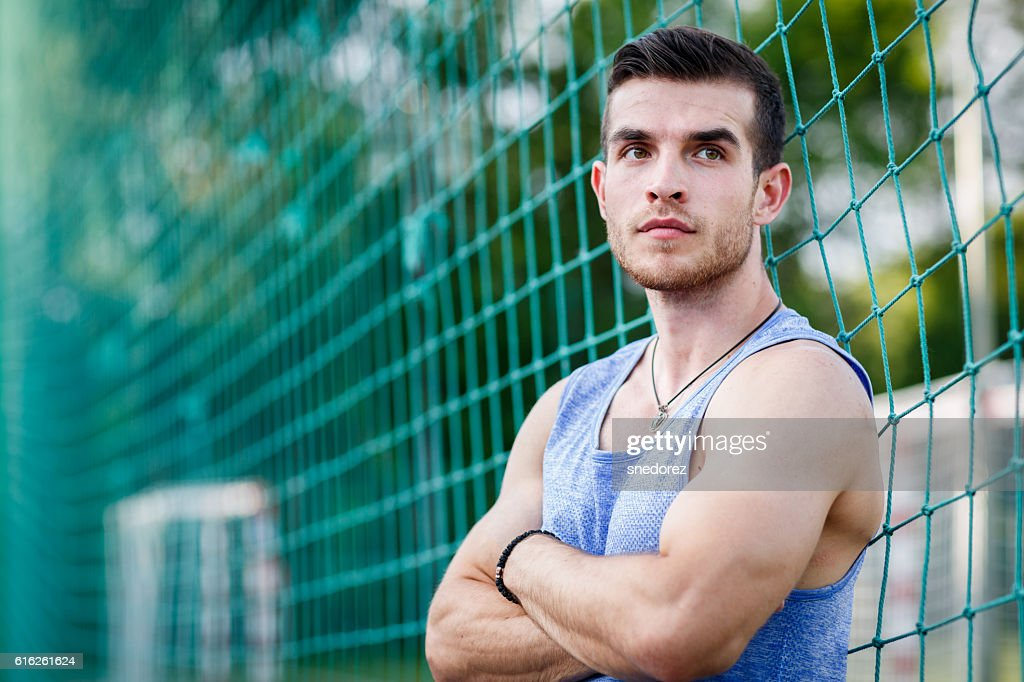Portrait of caucasian muscular man leaning on sports football nets : Foto de stock