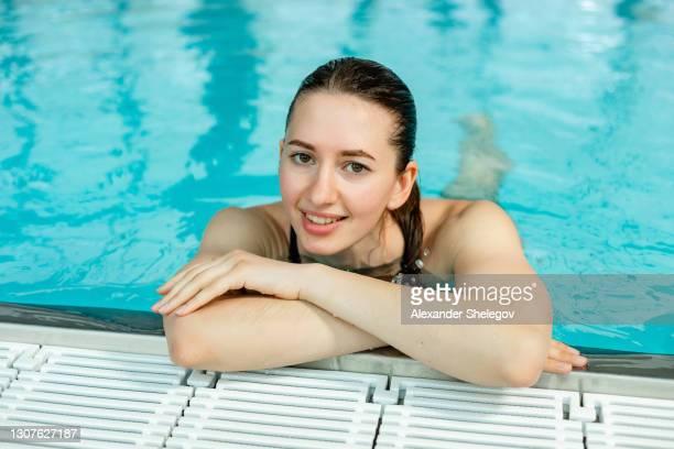 verticale du bon instructeur caucasien de forme physique dans la piscine. la femme heureuse détendant dans l'eau - match de groupe photos et images de collection