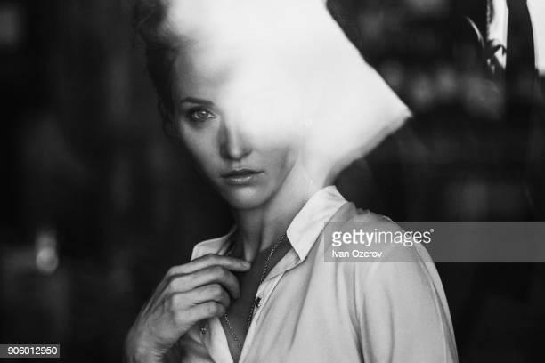 Portrait of Caucasian woman behind window