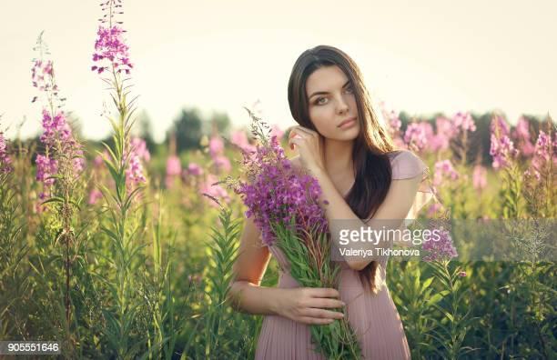 Portrait of Caucasian woman gathering wildflowers in field
