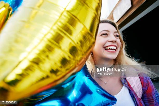Portrait of Caucasian woman laughing and holding balloon