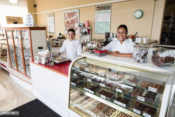 Portrait of Caucasian women co-owners of a candy shop standing behind counter.