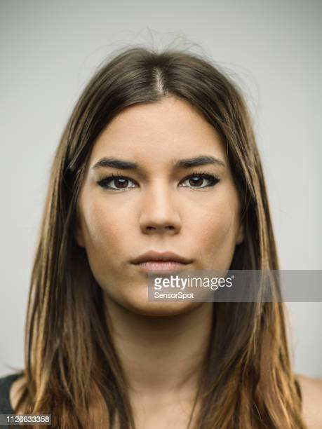 portrait of caucasian young woman with blank expression - police mugshot stock pictures, royalty-free photos & images