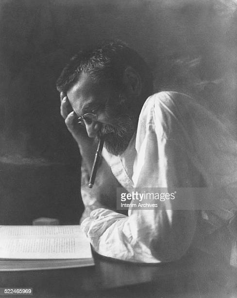 Portrait of Charles Proteus Steinmetz engineer and mathematician as he smokes a cigar while reading a book circa 1915
