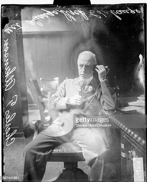 Portrait of Charles T Atkinson, Secretary of the Chicago Stock Exchange sitting in his office, leaning back in his chair and speaking on the...