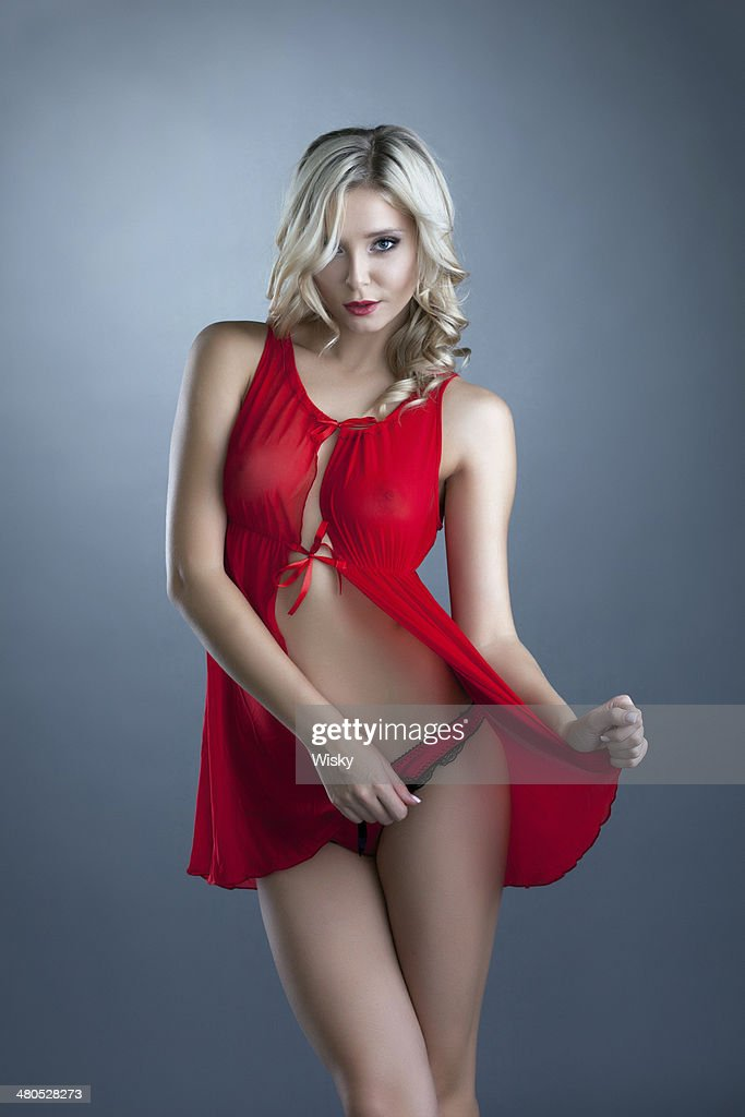 Portrait of charming blonde posing in red negligee : Stock Photo