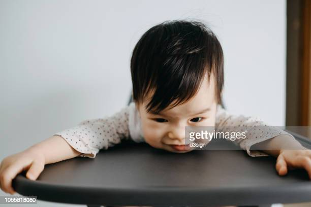 portrait of cheeky asian baby girl making faces while sitting on high chair - bent over babes stock pictures, royalty-free photos & images